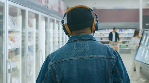 At the Supermarket: Stylish African American Guy with Headphones Walks Through Frozen Goods Section of the Store. Following Back View Shot. Slow Motion.