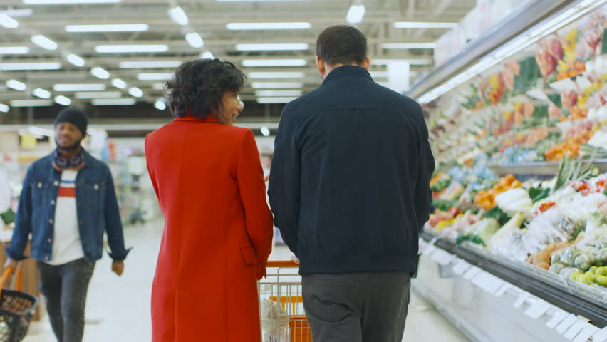 At the Supermarket: Happy Young Couple Walks Through Fresh Produce Section of the Store, Man Embraces Woman Lovingly. Back View Following Shot. Shot on RED EPIC-W 8K Helium Cinema Camera. #1015805098