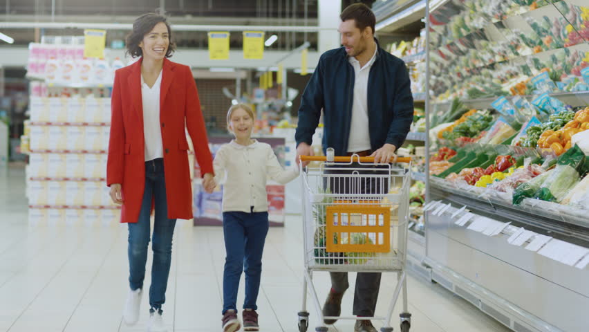 At the Supermarket: Happy Family of Three, Holding Hands, Walks Through Fresh Produce Section of the Store. Father, Mother and Daughter Having Fun Time Shopping. Shot on RED EPIC-W 8K Helium Camera. #1015805278