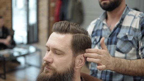 Close-up of barber doing styling with a handsome man with a long beard. Hairdresser's hands at working process. Barber making haircut of attractive bearded man in barbershop. Hairdresser at work.