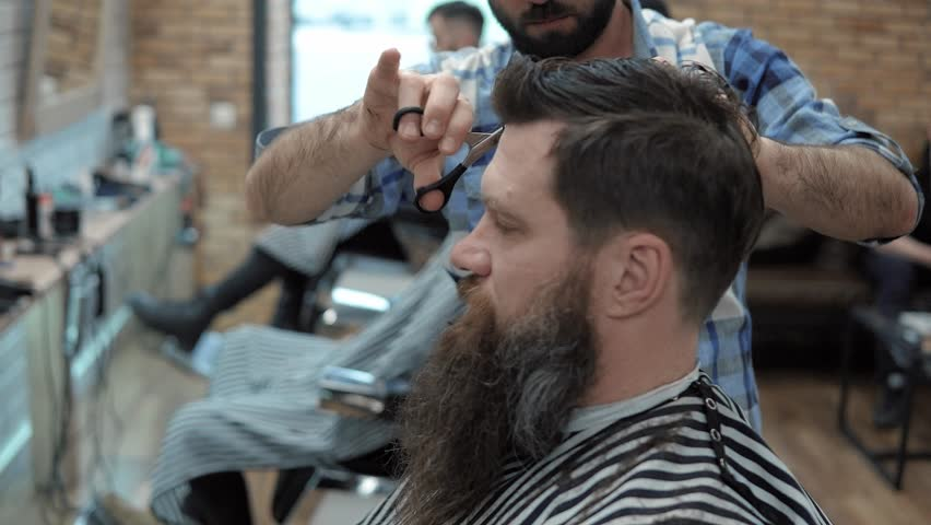 Close-up of barber cuts the hair by scissors at barbershop. Hairdresser's hands at working process. Barber making haircut of attractive bearded man in barbershop. Hairdresser at work. Beauty saloon.   Shutterstock HD Video #1015820488