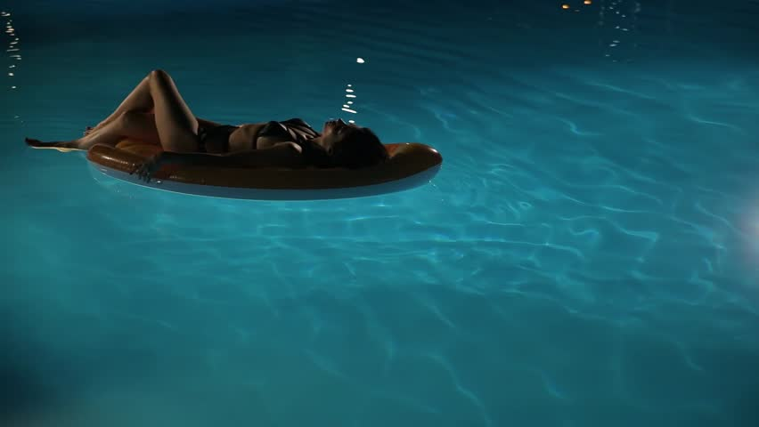 Young woman swimming on air mattress in pool | Shutterstock HD Video #1015832338