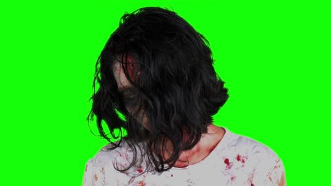 Scary zombie woman face with bloody mouth and white eye looking at the camera in the studio. Shot in 4k resolution with green screen background