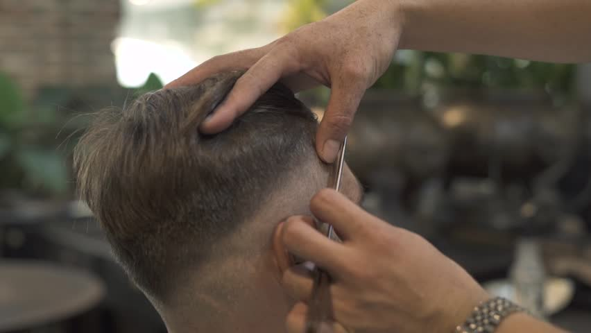 Barber shaving face with straight razor while hipster hairstyle in barber salon. Close up of shaving hair on head with razor in male salon. Man hands using straight razor for male hairdo | Shutterstock HD Video #1015835758
