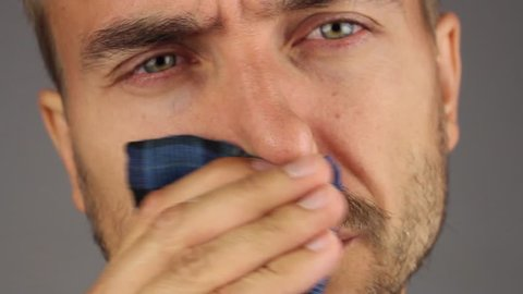 man with beard and mustache sneezes then blows his nose and wipes nose with a blue handkerchief, face closeup, gray background, front view