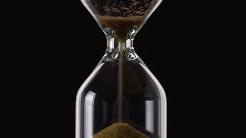Transience of time. Hourglass on a black background closeup