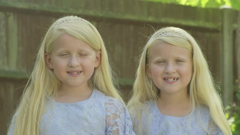 Portrait of pre teen twin caucasian girls looking at the camera themes of sisters siblings twins affection