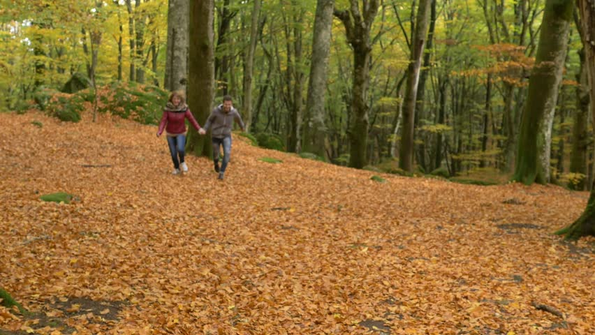 happy lovers running and jumping in the autumn park- slow motion