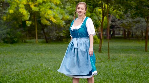 Blonde haired woman in blue bavarian costume dancing. Oktoberfest theme