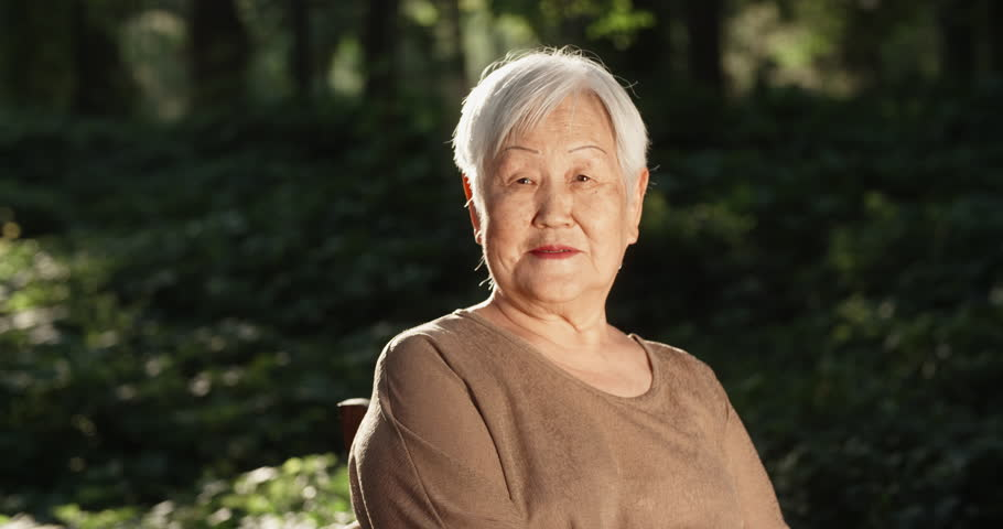 Happy old panasian woman sitting in park, looking at camera and smiling - portrait 4k | Shutterstock HD Video #1015879858