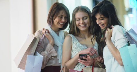 Three female friends standing near mall with shopping bags in hands, looking through photos on smartphone and laughing 4k