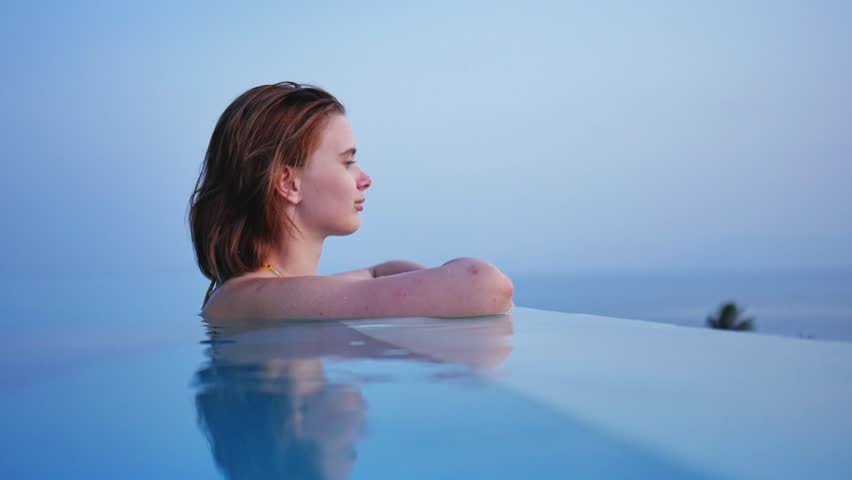 Young girl in swimming-pool looking into the distance