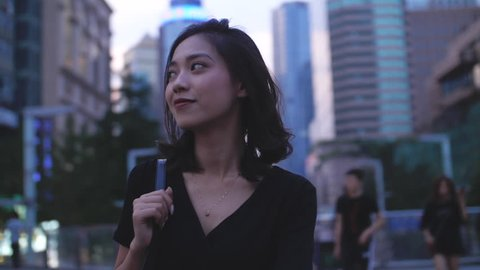 One pretty young asian girl walking in the city street with black dress in slow motion