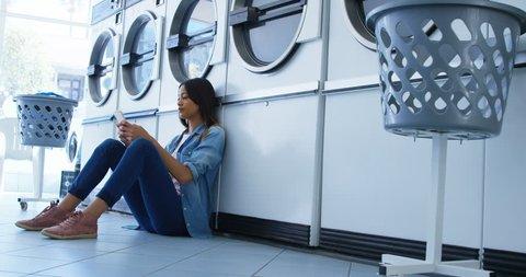 Smiling woman using mobile phone at laundromat 4k
