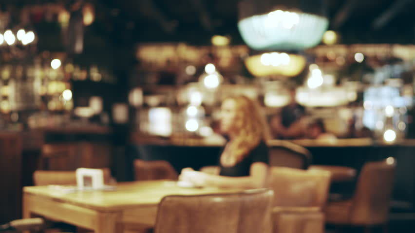 Blurred image of the interior of a large beautiful restaurant with bright lighting. A young woman in a dress sits at a table in a restaurant, drinks coffee and reads a news line in a smartphone