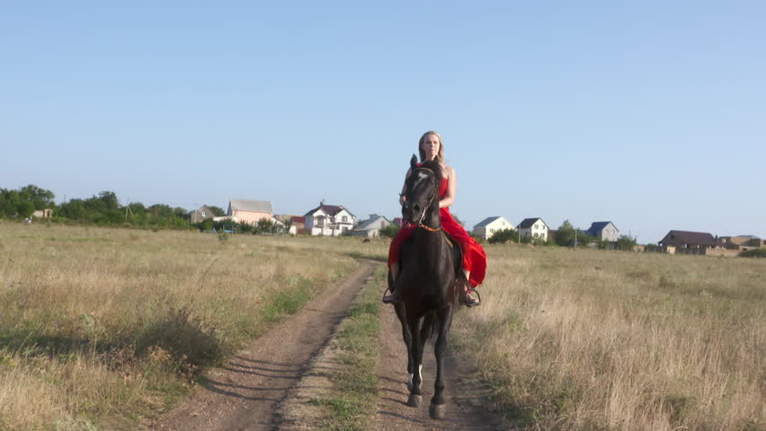 Young girl in red dress riding horse across field in summer