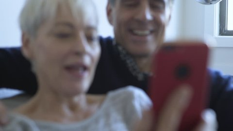Handheld close-up shot of couple using mobile phone at home