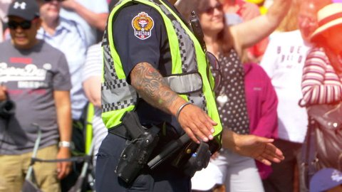 Victoria, BC Canada, July 8 2018 - Police Officer Directing Busy Urban Traffic, Crowd Control Policeman Street Cop