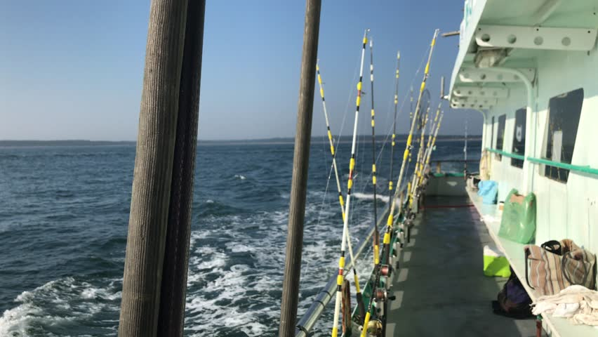 Fishing boat with fishing poles lined up on water off of Montauk, Long Island, New York | Shutterstock HD Video #1016009338