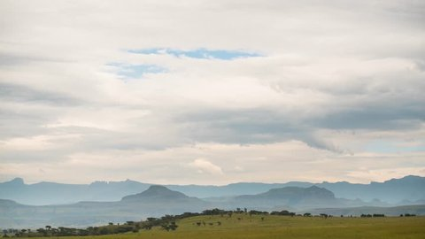 Timelapse of sun rays over majestic Drakensberg mountain range as rapidlying cloudse accross in South Africa