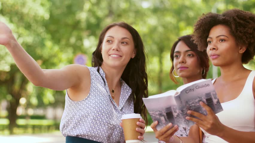 Tourism and travel concept - tourists with city guide asking local woman for help