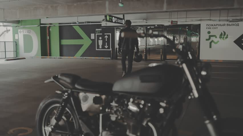 Biker guy walking through the parking to his motorcycle. Motorcyclist and vintage motorbike from 1970s in the garage. Side view urban lifestyle scene. Slow motion video shooting by handheld gimbal