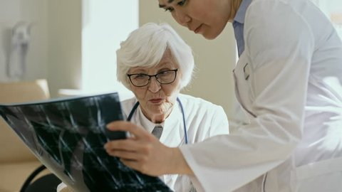 Experienced senior female doctor in eyeglasses telling about x-ray image to young asian assistant