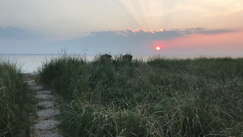 Sunrise, sunset through beach grass, rock pathways, rays of light streaming though clouds with 2 chairs overlooking water | Shutterstock HD Video #1016036038