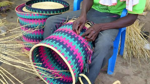 African Art. A man weaves baskets and hats in a marketplace in Ghana.