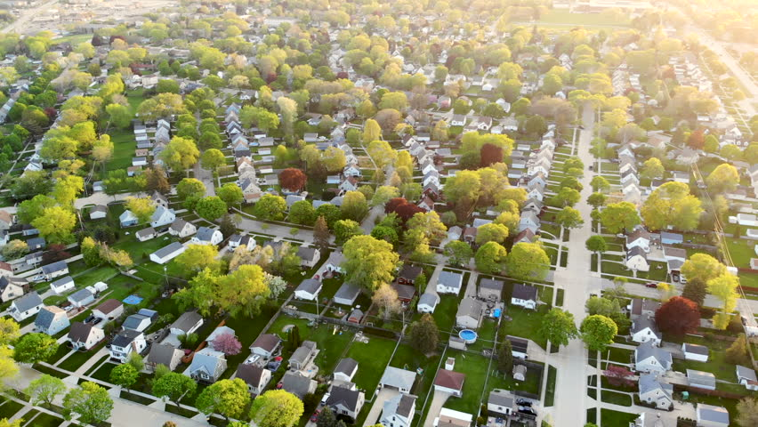 Aerial view of residential houses at spring (may). Establishing shot of american neighborhood, suburb.  Real estate, drone shots, sunset, sunlight, from above.