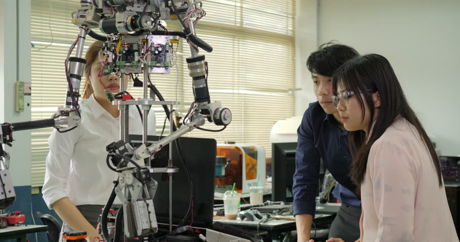 Team of robotics engineer works with robot, assembling and testing robotics responses with laptop Computer in workshop. People with technology or innovation concept. | Shutterstock HD Video #1016078818