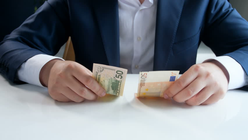 Conceptual 4k video of young businessman choosing investing and saving money in US dollar currency instead of Euro #1016086228