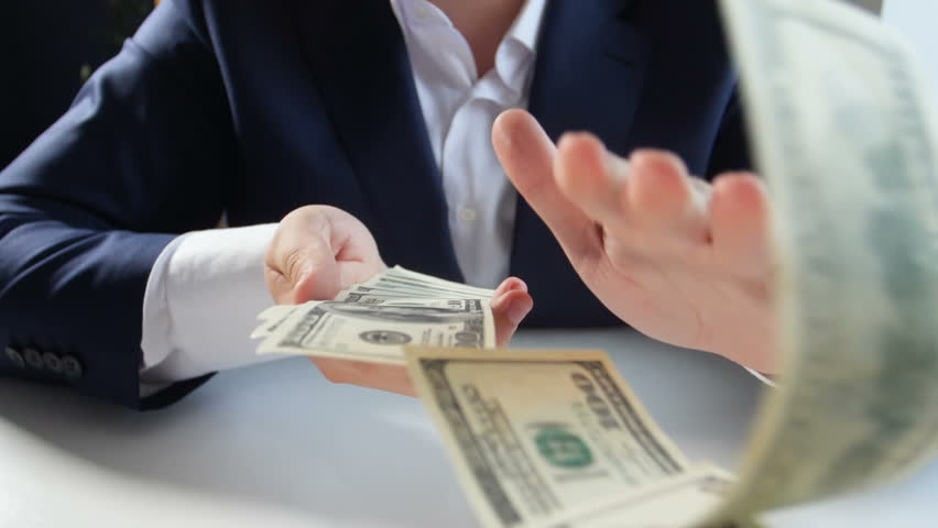 Slow motion video of successful businessman throwing money from big stack of dollars #1016086378