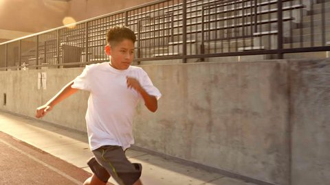 12 year old boy runs on his school's track.