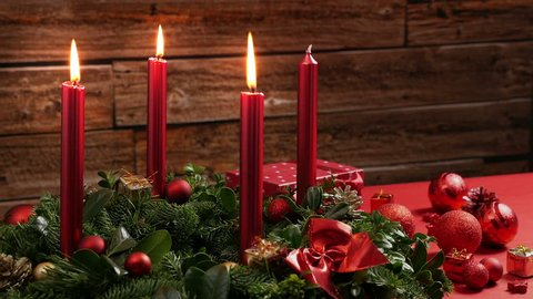 Three burning red candles on a traditional advent wreath of green fir twigs and mistletoes with festive decoration in front of a rustic wooden wall, close-up real time shot with copy space, nobody