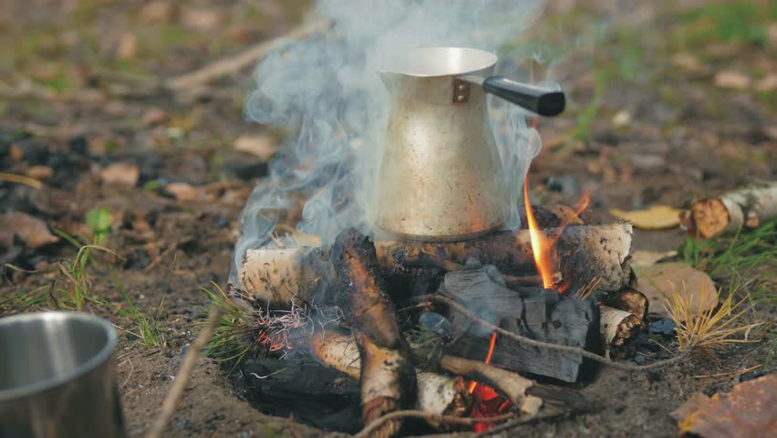 Making coffee in cezve on fire. Bonfire in a beautiful autumn forest. Camp Fire.