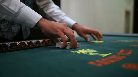 Casino: Dealer shuffles the poker cards.  Video shooting without stabilization, there is vibration and a little noise