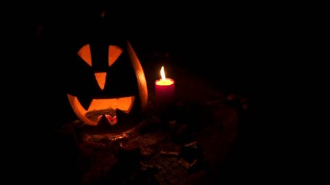 SLOW MOTION: Halloween pumpkin head jack lantern with burning candles. Candles are being magically lit. Halloween holidays art design, celebration. Stock video footage.