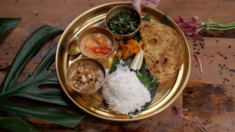 Assorted indian sri-lanka food set on wooden background. Dishes and appetisers of indeed cuisine, rice, lentils, paneer, samosa, spices, masala. Bowls and plates with indian food top view chicken