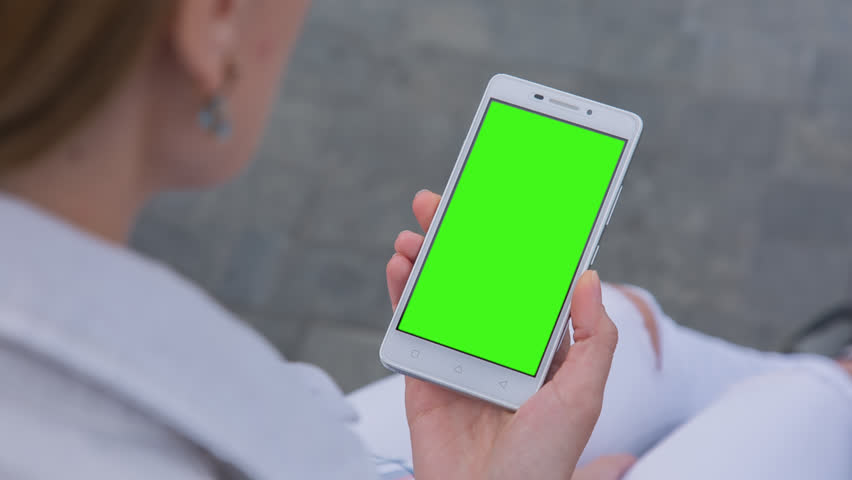 Young Woman in white jeans sitting on bench holds SmartPhone with pre-keyed green screen. Perfect for screen compositing. Made from 14bit RAW #1016197678