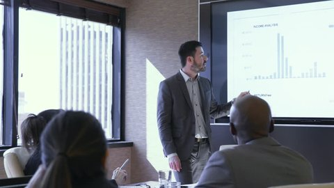 Dolly shot of businessman explaining graph to colleagues in meeting at board room
