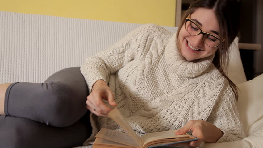 A young girl in a white sweater on a winter evening at home with glasses reads a funny book and laughs. Book. Evening. Girl. reading | Shutterstock HD Video #1016204848