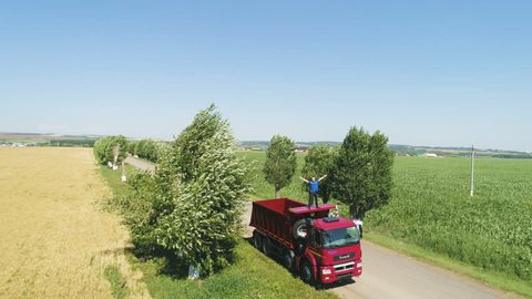 Aerial view red broken tipper truck driver stands on cabin roof and waves hands for help on road across fields