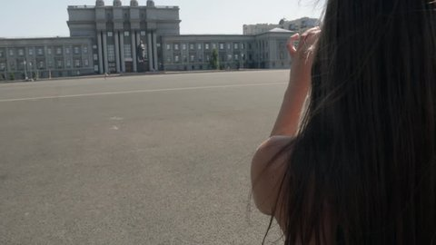Back view of young white caucasian woman with long dark hair standing on Kuibyshev square and taking picture with small white photo camera in sunny summer day in Samara city, Russia
