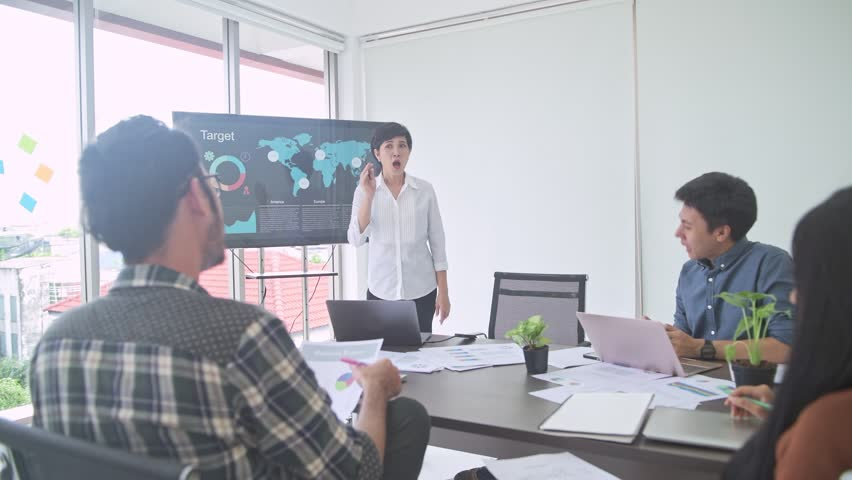 Business meeting. Small start up business meeting in room. Asian team with man and woman brainstorming the next big idea. Senior woman presenting to team. New business model start up concepts. | Shutterstock HD Video #1016237428