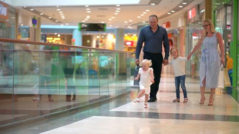 Happy family of four doing shopping. Family in mall. Children At Mall With Parents. Family shopping in big store. Family walking through shopping mall carrying sale bags. shopping girl. slow-motion