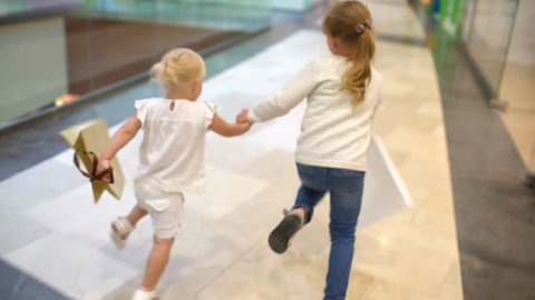Shopping day of a happy family. little girls with packages walks with family on big shopping mall center. children running with bags on mall. shopping girl bag. happy family shopping child slow-motion