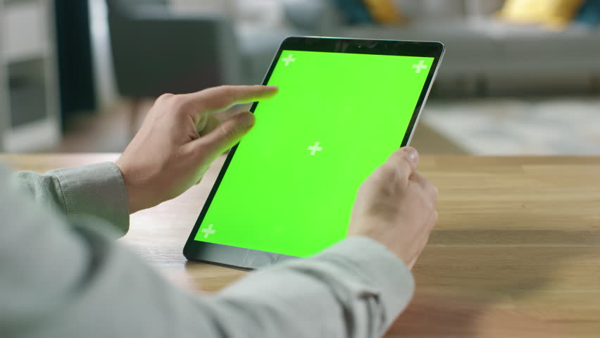 Man Using Hand Gestures on Green Mock-up Screen Digital Tablet Computer in Portrait Mode while Sitting at His Desk. In the Background Cozy Living Room. | Shutterstock HD Video #1016261968