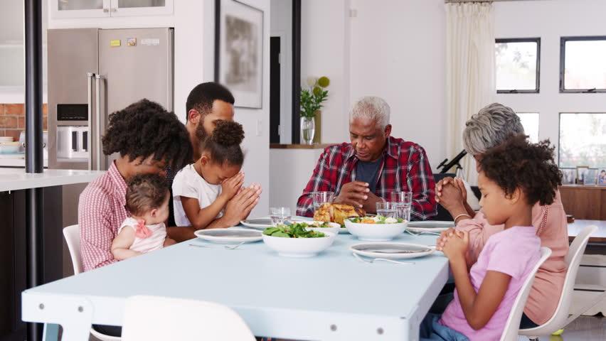 family praying around table - 852×480