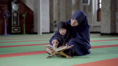 Asian Indonesian Muslim mother is teaching on how to read the quran to her daughter in the holy Mosque. Islam,religion and knowledge concept.